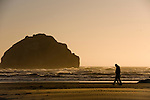 A couple walks by Face Rock as sunset shines on waves at Bandon Beach, Oregon.