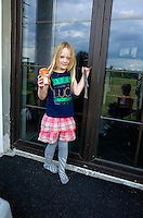 Happy young girl fashionably dressed age 6 holding can of soda at front door. Zawady Central Poland