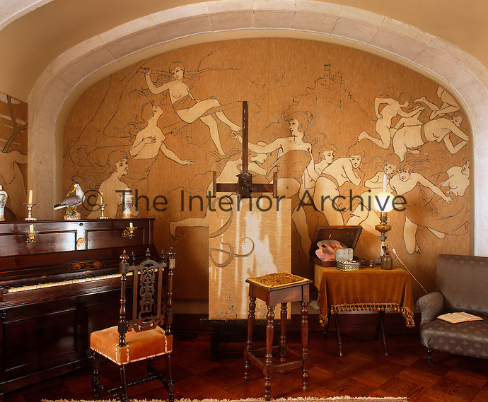 An Art Noueau mural of nymphs floating and dancing decorates an arched wall in the music room