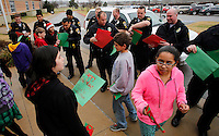 NWA Media/DAVID GOTTSCHALK - 12/18/14 - Fifth grade students at Old Wire Road Elementary School hand out Christmas cards to officers in the Rogers Police Department as they participate in Caroling for Cops Thursday December 18, 2014 at the school in Rogers. The fifth graders  performed Christmas songs, handed out Christmas cards and served hot chocolate during the holiday program.