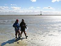 Kinder im Watt, laufen bei Ebbe, Niedrigwasser über Wattflächen, im Hintergrund der Leuchtturm von Westerhever, Nationalpark Schleswig-Holsteinisches Wattenmeer