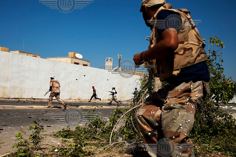 Rebel fighters approach the walls of Gaddafi's residence in Tripoli. After a six month revolution, rebel forces finally managed to break into Tripoli and have taken control of Bab al-Aziziyah, Col Gaddafi's compound and residence. Few remain that are loyal to Gaddafi in the city; it is seeming that the 42 year regime has come to an end. Gaddafi is currently on the run.