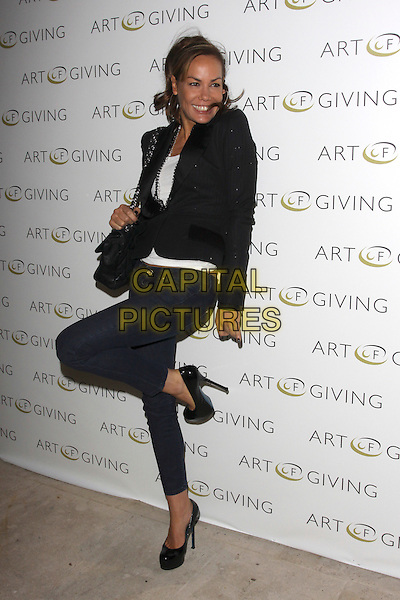 TARA PALMER TOMKINSON.at The Art Of Giving - Private View, Saatchi Gallery, London, England, UK, October 7th 2010..full length skinny jeans black patent platform shoes heels blazer jacket white top bag chanel necklace  smiling standing on one foot leg .CAP/AH.©Adam Houghton/Capital Pictures.
