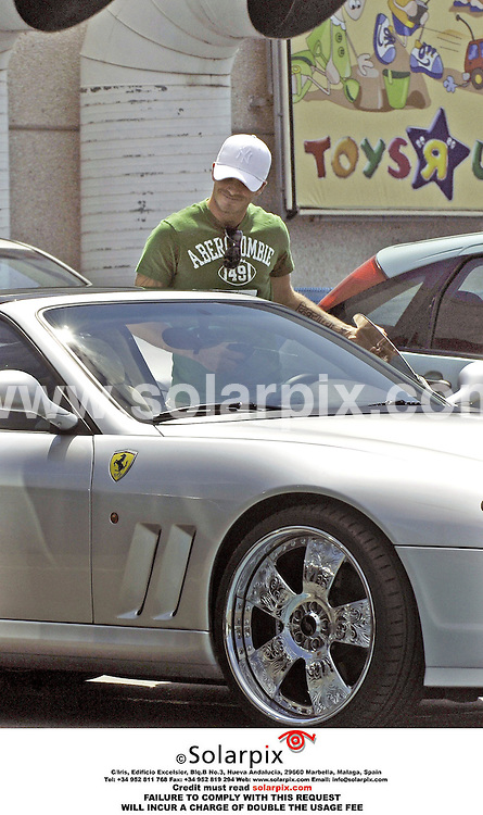 ALL ROUND EXCLUSIVE PICTURES BY SOLARPIX.COM. .24.08.06.David Beckham shopping at Toys R Us in Madrid  for birthday presents for Romeo, his second oldest son, who will be four on 01.09.06. Beckham surprised two young car enthusiasts who had been checking out his silver Ferrari, when he returned to the car . JOB REF:2743-ROL..MUST CREDIT SOLARPIX.COM OR DOUBLE FEE WILL BE CHARGED.