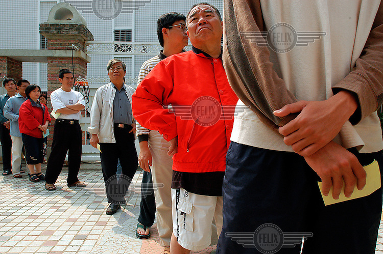 The high national election turnout of 80% is reflected in a queue at a polling station in Tainan. Incumbent president Chen Shui-bian retained power by a tiny majority, having survived a shooting incident on the campaign trail.