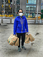 New York, New York City. A woman anticipates the worst apex of the coronvirus by stocking up supplies at Whole Foods. 4/4/20