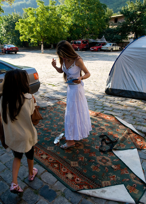 "A girl wearing her silver shoes and white dress to parade in front of the Bachkovo monastery where the traditional ""bride market"" of the Tinsmith clan of Bulgarian Roma is taking place. She and many other girls spent the night in a tent on the parking lot of the monastery."