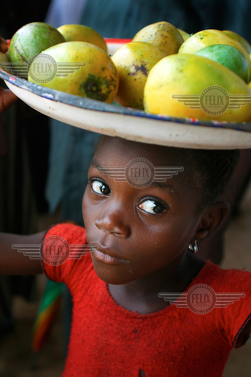 A girl carries fruit on her head.  Fruit for sale. Sierra Leone.