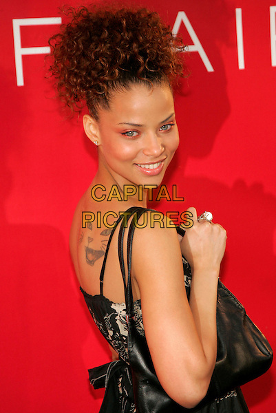 """DENISE VASI.At Revlon party to launch """"Flair"""" Fragrance at Mr. Chow, New York, NY ,USA..May 22nd, 2006.Photo: Jackson Lee/AdMedia/Capital Pictures.Ref: JL/ADM.half length looking over shoulder tattoo cat.www.capitalpictures.com.sales@capitalpictures.com.© Capital Pictures."""
