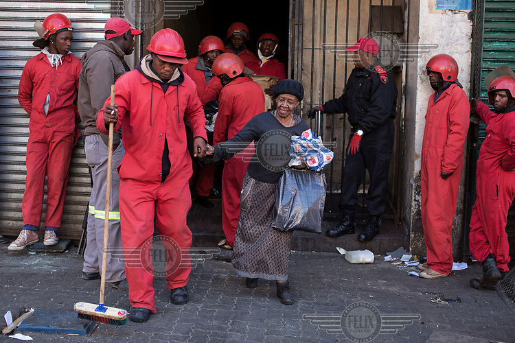 During an eviction, a Red Ant assists an elderly lady out of the squatted building where she had been living. The Red Ants are a controversial private security company often hired to clear squatters from land and so-called 'hijacked' properties.