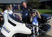NWA Democrat-Gazette/ANDY SHUPE<br /> Cpl. Jason Alvarado with the Fayetteville Police Department helps Ashlyn LeFevre, 2, Wednesday, Sept. 23, 2015, as she tries on his helmet during the first day of the annual First School Trike Rally at First United Presbyterian Church in Fayetteville. The event, which serves as a fundraiser for St. Jude's Children's Hospital, features bike riding, temporary tattoos, snow cones, a bike wash and demonstrations from the Fayetteville Police Department. Visit nwadg.com/photos to see more photographs from the morning.