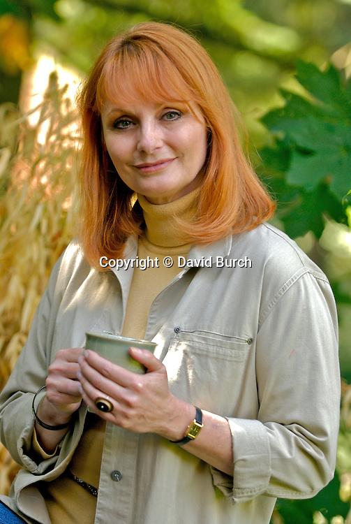 Mature woman smiling holding tea cup, portrait