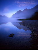 Early morning fog lifts of the tranquil waters of Lake Gunn in Fiordland National Park. Southland region, South Island, New Zealand.