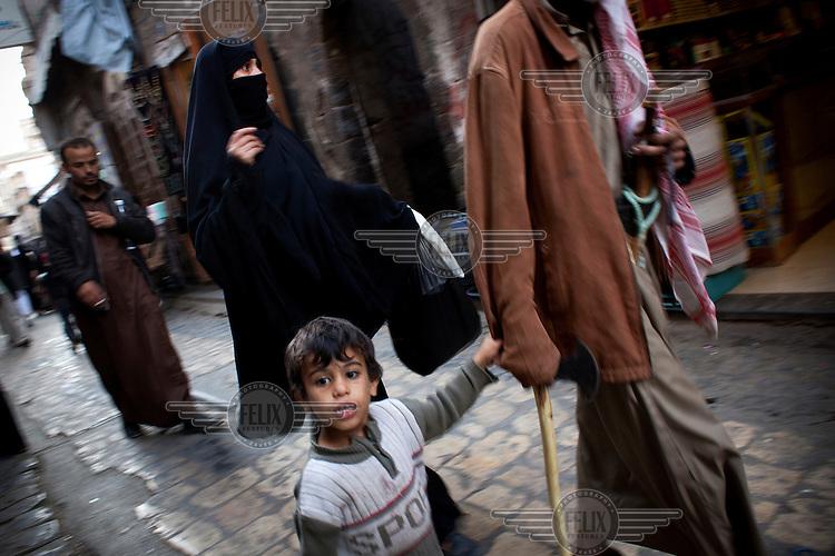 People walk along a street in Sana'a.