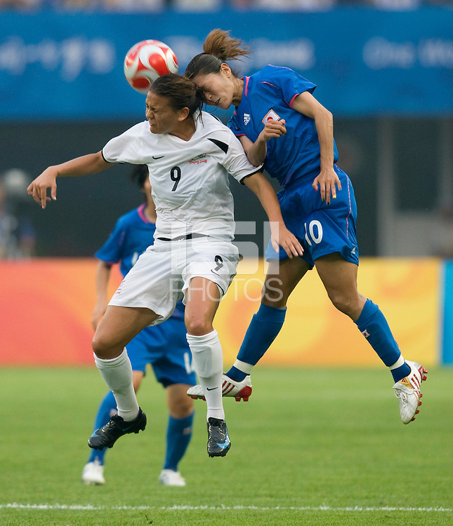 Japanese captain (10) Homare Sawa goes up for a header with New Zealand forward (9) Amber Hearn during first round play in the 2008 Beijing Olympics at Qinhuangdao, China. .  Japan tied New Zealand, 2-2, at Qinhuangdao Stadium.