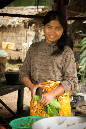 A young Cambodian woman is smiling while preparing a meal. Meal preparation in rural villages is typically done outside.