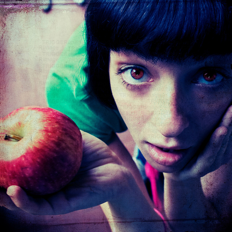 A young woman with black hair and red eyes holding a red apple looking at the camera