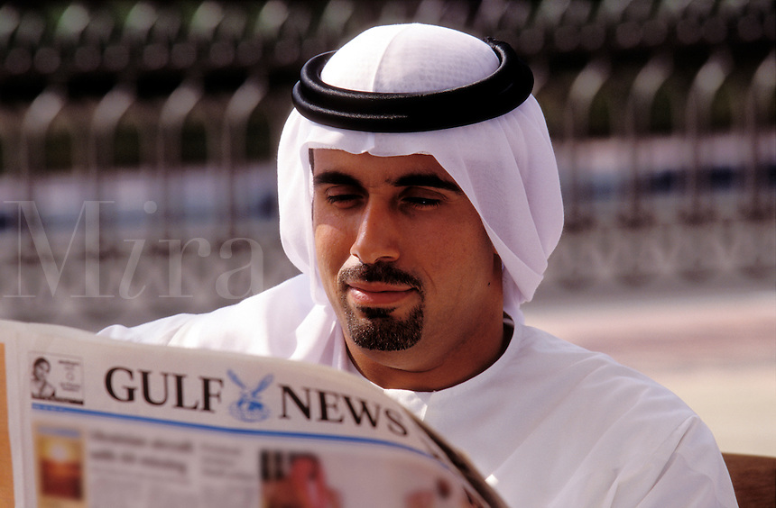 United Arab Emirates. Dubai.  Businessman reading local newspaper in English..
