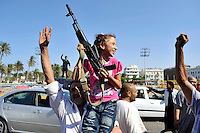 A girl holds a gun in the air as people celebrate in Tripoli. After a six month revolution, rebel forces finally managed to break into Tripoli and have taken control of Bab al-Aziziyah, Col Gaddafi's compound and residence. Few remain that are loyal to Gaddafi in the city; it is seeming that the 42 year regime has come to an end. Gaddafi is currently on the run.