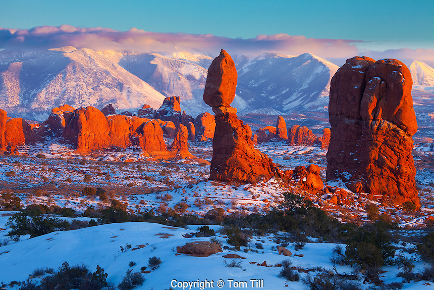 Balanced Rock in winter,  Arches National Park, Utah, La Sal Mountains beyond, Sunset