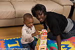 2 year old toddler boy with mother interaction playing with toys language development mother talking and involved African American horizontal