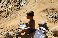 MADAGASCAR, region Manajary, town Vohilava, small scale gold mining / MADAGASKAR Mananjary, Vohilava, kleingewerblicher Goldabbau, Familien graben einen neuen Stollen, Kind beim Essen