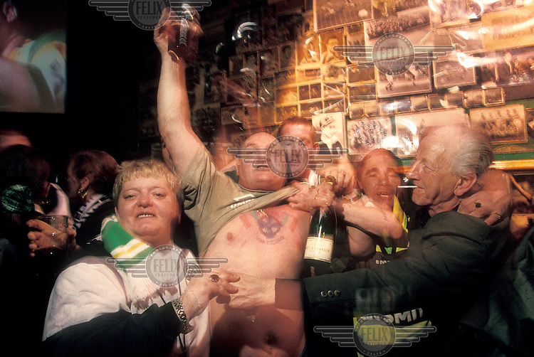 ©ÊPaul Lowe / Panos Pictures..Glasgow, Scotland. The Old Firm...Raucous Celtic supporters celebrating in Baird's Bar, a famous pub in Glasgow's East End decorated with Celtic memorabilia..The 'Old Firm' rivalry between Celtic and Rangers is renowned as the world's most intense football derby.