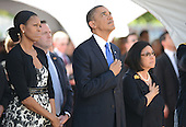 President Barack Obama looks up during a flyby conducted by Hawaii Air National Guard F-22 Raptors on Sunday, December 23, 2012.  First Lady Michelle Obama stands at left and Irene Hirano Inouye, wife of the late U.S. Senator Daniel Inouye (Democrat of Hawaii), stands at right near the casket of the late Senator Inouye at the National Memorial Cemetery of the Pacific during ceremonies in honor of the late Senator.  Senator Inouye was a Medal of Honor recipient and a United States Senator since 1963.    .Credit: Cory Lum / Pool via CNP
