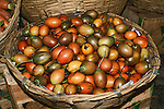 A shallow, wicker basket of oval-shaped tomatoes in reds, greens and yellows with stems found in a outdoor market in Bhutan.