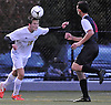 Jake Bresnihan #16 of Massapequa, left, makes a header during the Nassau County Class AA varsity boys soccer playoffs against Syosset at Adelphi University on Sunday, Oct. 30, 2016. Thunder, lightning and heavy rain necessitated a delay nine minutes into the second half a scoreless match.