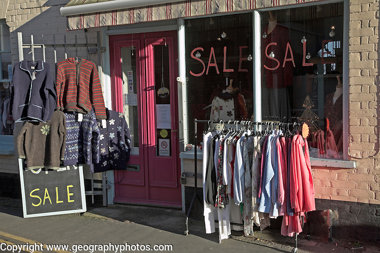 Clothes shop sale with clothing on racks outside, Aldeburgh, Suffolk, England