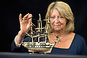 """19/09/14 <br /> <br /> Ros Beardsley, from Hansons Auctioneers inspects the ship ahead of next week's auction.<br />  <br /> A rare model of a war ship is expected to fetch thousands when it goes under the hammer at auction next week.<br /> <br /> The two-hundred-year-old model war ship made from old cattle bone discovered in a Lichfield attic is anticipated to sell for up to £5,000 at Hansons Auctioneers in Derbyshire on Saturday, September 27.<br /> <br /> A model of a British naval ship dating from circa 1800-1810 and constructed from recycled cattle bone and box wood has been uncovered in a Lichfield loft.<br /> <br /> Charles Hanson, manager of Hansons Auctioneers, said the model ship would actually have been carved by captured French prisoners who had served Napoleon.<br /> <br /> The retired couple who own the ship were reportedly delighted to learn its anticipated value, commenting: """"Despite being in land-locked Derbyshire, we hope the wind will blow and the ship will set sail with a gale behind it!""""<br /> <br /> The price guide on the ship is £3,000 to £5,000, and is expected to create international interest.<br /> <br /> Mr Hanson described the intricacy of the detailing on the item, housed within a glass and walnut case, as superb.<br /> <br /> He said: """"The fine carved work and symmetrical hull and deck is remarkable together with the delicate rigging.<br /> <br /> """"The prisoners who made such works of art were not treated like convicts, they were confined to the likes of prison hulks in naval dockyards, old castles or purpose built prison camps such as Norman Cross or Dartmoor.<br /> <br /> """"On the encouragement of their captors, they formed their own guilds to produce small objects d'art to sell in the camp's periodic civilian open market.""""<br /> <br /> <br /> <br /> <br /> <br /> All Rights Reserved: F Stop Press Ltd. +44(0)1335 300098   www.fstoppress.com."""