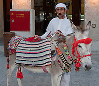 Doha, Qatar.  Qatari Man Wearing a Traditional Dishdasha Offers Rides on a Donkey to Qatari Children in the Market.