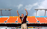 St. Augustine High School head coach Joey Wiles wears a grin as he pumps his fists into the air after receiving a state championship his team's victory in the class 3A state championship game at Dolphins Stadium in Miami, Fl.