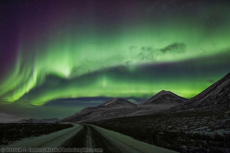 The aurora swirls over the dalton highway in Atigun Canyon, Brooks Range, Arctic, Alaska.