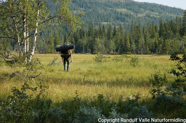 Mann bærer kano i ryggsekk ved elva Forra. ----- Man portaging collapsable canoe.