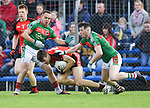 Cillian Brennan of Clondegad in action against Stephen Moloney and Keelan Sexton of Kilmurry Ibrickane during their senior county final at Cusack park. Photograph by John Kelly.