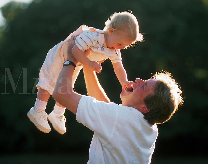 A laughing man playfully lifts a smiling toddler.