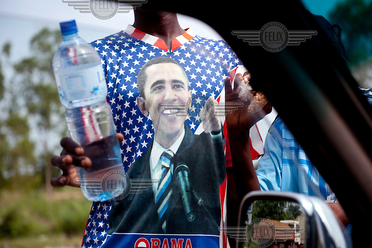 A child wearing an Obama Tshirt sells water by the side of the road.