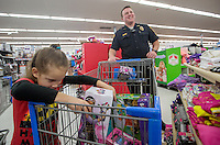 STAFF PHOTO JASON IVESTER --12/13/2014--<br /> Grace Lockman, 5, of Rogers looks over her toys in the shopping cart with Rogers Police Officer John Lawrence during the department's annual Shop With a Cop event on Saturday, Dec. 13, 2014, at the Walmart Supercenter on Walnut Street in Rogers. The officer had a $100 budget for each child for toys and clothes.