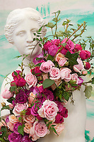 Classical Grecian statute of a woman holding real roses in many colors