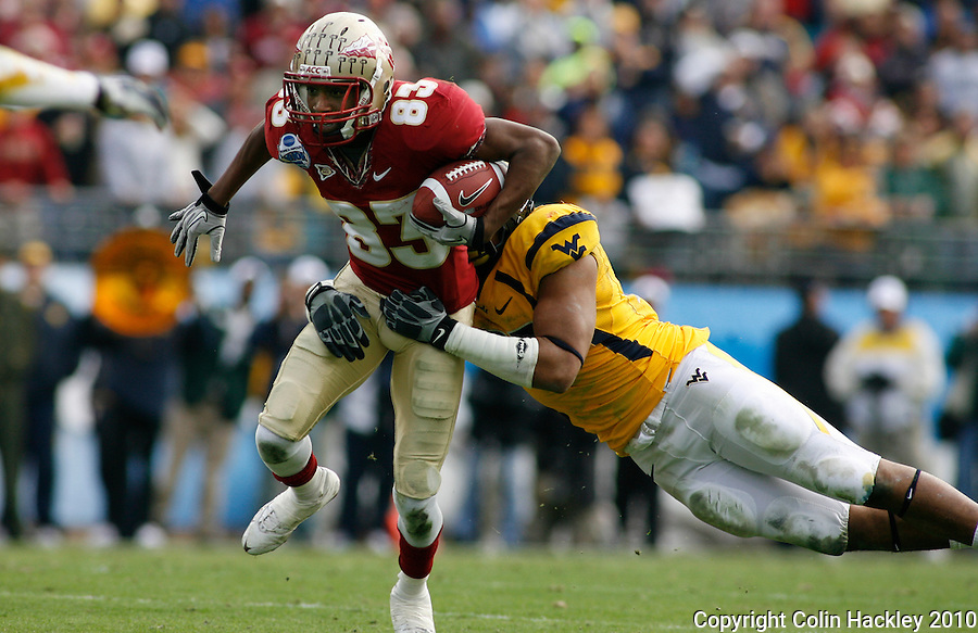 JACKSONVILLE, FL 1/1/10-FSU-WV FB CH38-Florida State's Bert Reed is tackled by West Virginia's Julian Miller during first half Gator Bowl action Friday in Jacksonville, Fla. .COLIN HACKLEY PHOTO
