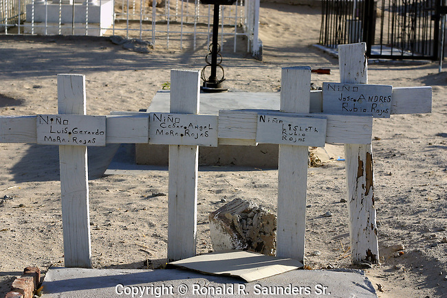 Four crosses mark the gravesites of the four children belonging to the Rojas family during the annual Day of the Dead commemoration