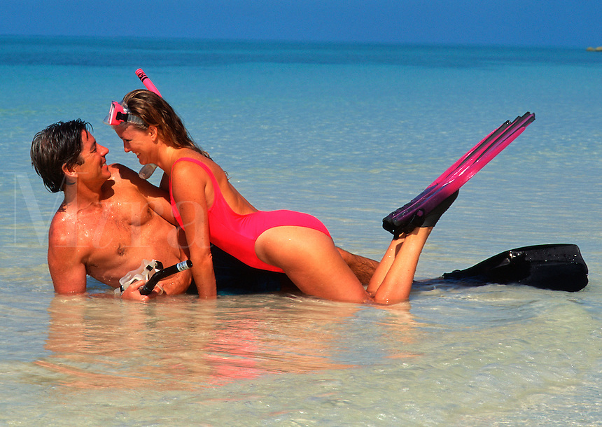 Romantic couple playing on the beach, with snorkeling equipment