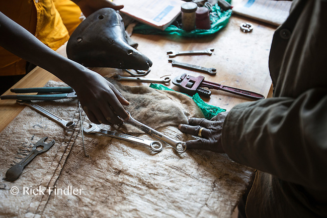 BURUNDI, Ruyigi: 10 June 2015 Ruyigi Re-education Centre Feature.<br /> See accompanying article for general information. <br /> Pictured: The hand of an inmate next to the hand of a teacher whilst learning how to repair bicycles. <br /> Rick Findler / Story Picture Agency