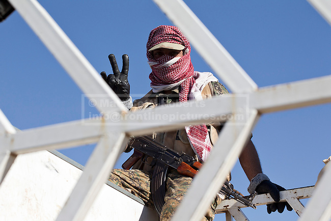 11/12/2014. Sinjar Mountains, Iraq. A Yazidi fighter makes a V for vistory sign from inside a truck on the top of Mount Sinjar.<br /> <br /> Although a well publicised exodus of Yazidi refugees took place from Mount Sinjar in August 2014 many still remain on top of the 75 km long ridge-line, with estimates varying from 2000-8000 people, after a corridor kept open by Syrian-Kurdish YPG fighters collapsed during an Islamic State offensive. The mountain is now surrounded on all sides with winter closing in, the only chance of escape or supply being by Iraqi Air Force helicopters.