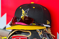 An Indianapolis Indians hat sits on top of a glove in the dugout during an International League game against the Buffalo Bisons on July 28, 2018 at Victory Field in Indianapolis, Indiana. Indianapolis defeated Buffalo 6-4. (Brad Krause/Four Seam Images)