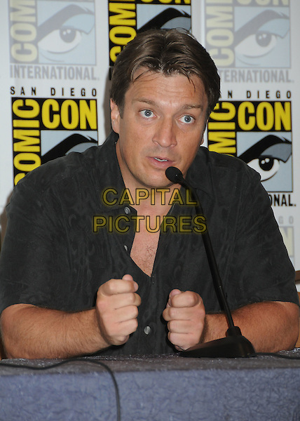 "Nathan Fillion.""Firefly"" Press Room at Comic Con 2012 held at the Bayfront Hilton Hotel, San Diego, California, USA..July 13th, 2012.half length black shirt sitting table hands microphone .CAP/ADM/BP.©Byron Purvis/AdMedia/Capital Pictures."