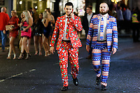 Two young men in festive suits walk in Wind Street, Swansea, Wales  on Mad Friday, Booze Black Friday or Black Eye Friday, the last Friday night before Christmas Day, when traditionally people in the UK go out to celebrate the start of their holidays. Friday 22 December 2017