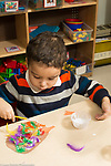 Education preschool 3 year olds boy gluing feathers to paper art activity